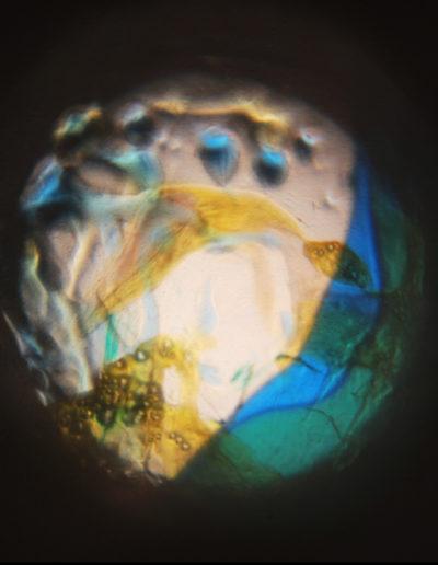 Mya Lurgo, CosmoMania Destinata II, Vetrino, mixed media, oli colorati, lente d'ingrandimento, proiezione a soffitto o parete, Ø massimo 200 cm, 2004