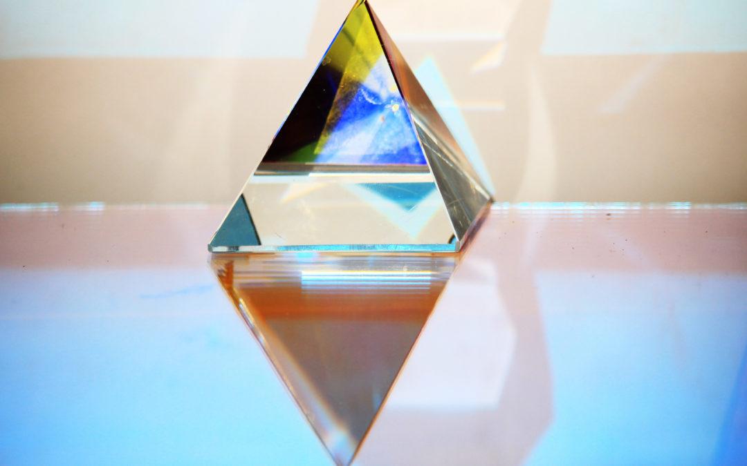 Un prisma riflette la luce creando una moltitudine di clori. Immagine di copertina della mostra di Mya Lurgo